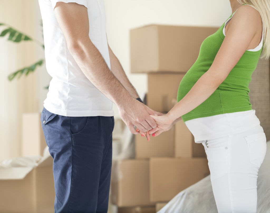 Pregnant wife holding hands of husband - Moving home